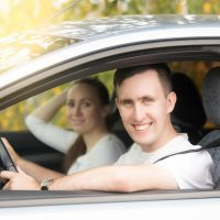 Young happy traveler man driving, a woman sitting near in the car, family travelling by car on summer vacation. Looking at the camera and smiling